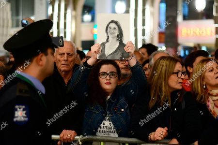 A protestors holds up a pictures of slain journalist Daphne Caruana Galizia during a demonstration outside Malta's prime minister's office in Valletta, Malta, . On Wednesday Maltese police arrested Prime Minister Joseph Muscat's former chief of staff Keith Schembri for questioning as a person of interest in the murder of journalist Daphne Caruana Galizia