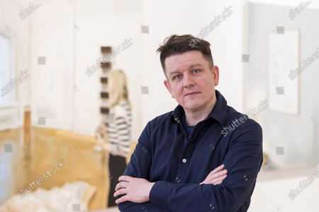 "Polish artist Marcin Maciejowski poses with his works (L) ""It Is Enough I'm Delighted, Don't Make Me Understand It"", and (R) ""Private View (Warhol)"" both 2019. First look of ""Private View"" by Marcin Maciejowski at Galerie Thaddeus Ropac in Mayfair. The artist's first London exhibition features new large-scale paintings and graphic works on paper merging comic-book and Old Master traditions. The show runs 28 November to 25 January 2020."