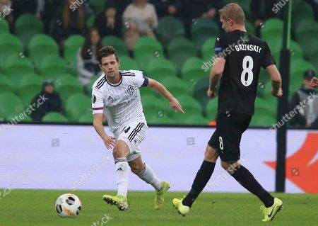 Krasnodar's Yury Gazinsky, right, fights for the ball with Basel's Valentin Stocker during the Europa League group C soccer match between Krasnodar and Basel at the Krasnodar stadium in Krasnodar, Russia