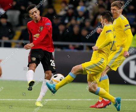 Stock Image of Manchester United's Mason Greenwood, left, kicks the ball ahead of Astana's Antonio Rukavina during the Europa League Group L soccer match between Astana and Manchester United in Astana, Kazakhstan
