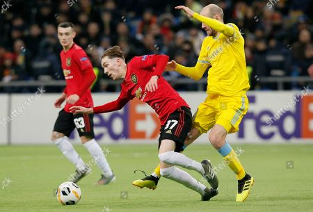 Manchester United's James Garner, centre, and Astana's Ivan Mayewski challenge for the ball during the Europa League Group L soccer match between Astana and Manchester United in Astana, Kazakhstan
