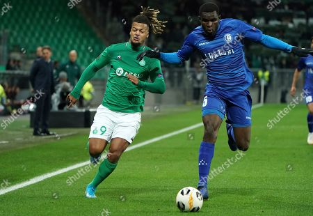 Saint-Etienne's Lois Diony, left, duels for the ball with Gent's Michael Ngadeu-Ngadjui during the Europa League group I soccer match between Saint Etienne and Gent at Geoffroy Guichard stadium in Saint Etienne, central France