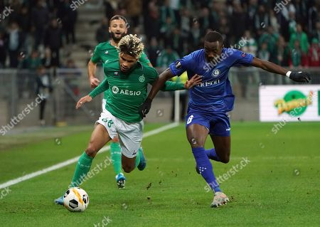 Saint-Etienne's Mahdi Camara, left, duels for the ball with Gent's Elisha Owusu during the Europa League group I soccer match between Saint Etienne and Gent at Geoffroy Guichard stadium in Saint Etienne, central France