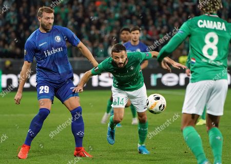 Saint-Etienne's Franck Honorat, center, duels for the ball with Gent's Laurent Depoitre, left, during the Europa League group I soccer match between Saint Etienne and Gent at Geoffroy Guichard stadium in Saint Etienne, central France