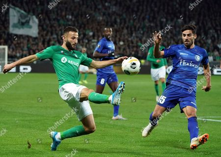 Gent's Milad Mohammadi, right, tries to block a shot from Saint-Etienne's Franck Honorat during the Europa League group I soccer match between Saint Etienne and Gent at Geoffroy Guichard stadium in Saint Etienne, central France