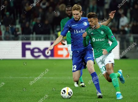 Gent's Igor Plastun, left, duels for the ball with Saint-Etienne's Denis Bouanga during the Europa League group I soccer match between Saint Etienne and Gent at Geoffroy Guichard stadium in Saint Etienne, central France