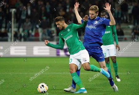 Saint-Etienne's Denis Bouanga, front, duels for the ball with Gent's Igor Plastun during the Europa League group I soccer match between Saint Etienne and Gent at Geoffroy Guichard stadium in Saint Etienne, central France