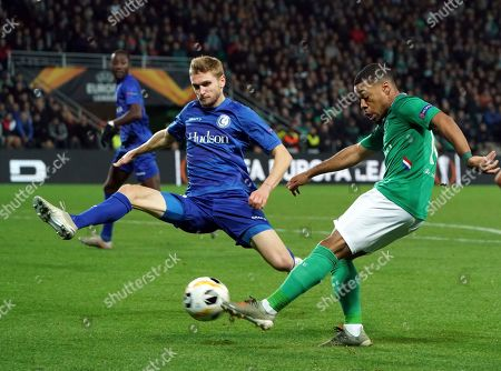Gent's Igor Plastun, left, tries to block a shot from Saint-Etienne's Arnaud Nordin during the Europa League group I soccer match between Saint Etienne and Gent at Geoffroy Guichard stadium in Saint Etienne, central France