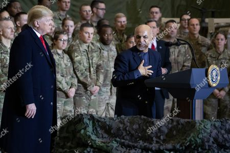 Donald Trump, Ashraf Ghani. President Donald Trump, left, listens as Afghan President Ashraf Ghani, right, addresses members of the military during Trump's surprise Thanksgiving Day visit, at Bagram Air Field, Afghanistan