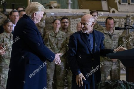 Donald Trump, Ashraf Ghani. President Donald Trump, left, reaches to shake hands with Afghan President Ashraf Ghani, right, during a surprise Thanksgiving Day visit, at Bagram Air Field, Afghanistan