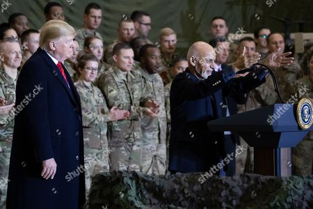 Donald Trump, Ashraf Ghani. President Donald Trump, left, watches as Afghan President Ashraf Ghani, right, addresses members of the military during Trump's surprise Thanksgiving Day visit, at Bagram Air Field, Afghanistan