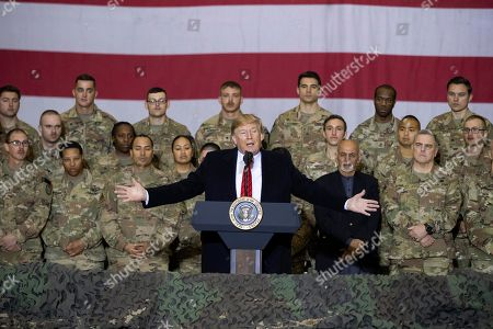 Donald Trump, Mark Milley, Ashraf Ghani. President Donald Trump, center, with Afghan President Ashraf Ghani and Joint Chiefs Chairman Gen. Mark Milley, behind him at right, while addressing members of the military during a surprise Thanksgiving Day visit, at Bagram Air Field, Afghanistan