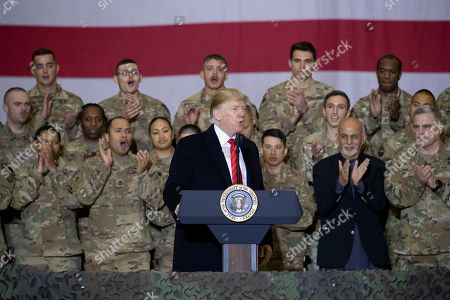 President Donald Trump, center, with Afghan President Ashraf Ghani, second from the right, and Joint Chiefs Chairman Gen. Mark Milley, right, while addressing members of the military during a surprise Thanksgiving Day visit, at Bagram Air Field, Afghanistan