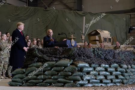 President Donald Trump, left, listens as Afghan President Ashraf Ghani addresses members of the military during Trump's surprise Thanksgiving Day visit, at Bagram Air Field, Afghanistan