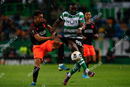 PSV's Donyell Malen, left, battles for the ball with Sporting's Yannick Bolasie during the Europa League group D soccer match between Sporting CP and PSV Eindhoven at the Alvalade stadium in Lisbon
