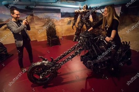 A visitor poses for a photo sitting on a scuplture of a motorcycle made of used car spare parts at an exhibition of the Amazing Metal Art Gallery in Budapest, Hungary, 28 November 2019.