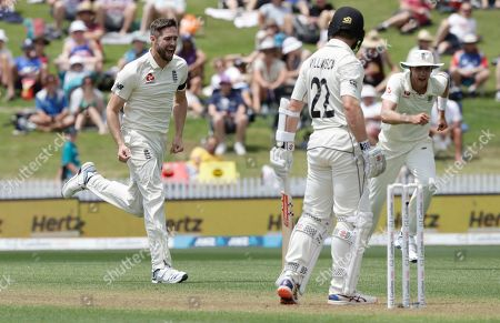 England's Chris Woakes, left, celebrates after dismissing New Zealand's Kane Williamson, centre, during play on day one of the second cricket test between England and New Zealand at Seddon Park in Hamilton, New Zealand