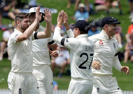 England's Chris Woakes, left, celebrates with teammates after dismissing New Zealand's Kane Williamson during play on day one of the second cricket test between England and New Zealand at Seddon Park in Hamilton, New Zealand