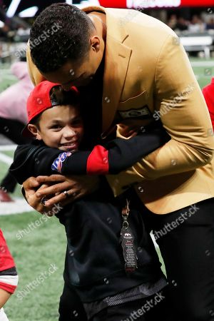 Former NFL player and Football Hall of Fame member Tony Gonzalez hold his son River Gonzalez after Tony was celebrated on the field at half time of an NFL football game between the Atlanta Falcons and the New Orleans Saints, in Atlanta