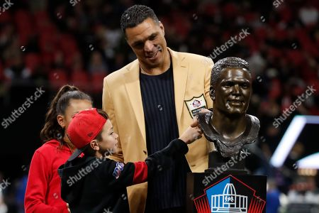 Former NFL player and Football Hall of Fame member Tony Gonzalez stands with his family as he was celebrated on the field at half time of an NFL football game between the Atlanta Falcons and the New Orleans Saints, in Atlanta