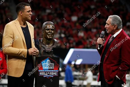 Former NFL player and Football Hall of Fame member Tony Gonzalez stands with his family as he is celebrated and Atlanta Falcons owner Arthur Blank speaks on the field at half time of an NFL football game between the Atlanta Falcons and the New Orleans Saints, in Atlanta