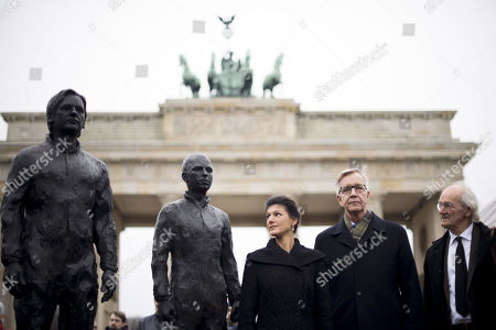 Sahra Wagenknecht and Dietmar Bartsch alongside bronze statues of Julian Assange and Chelsea Manning
