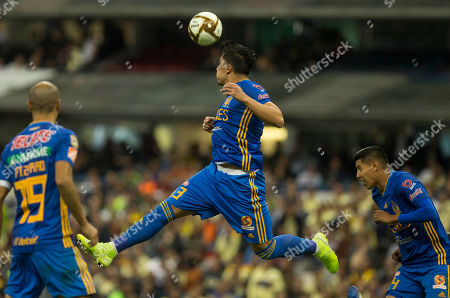 CP. Tigres' Carlos Salcedo, center, heads the ball during the team's Mexico soccer league match against America, in Mexico City