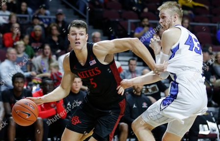 San Diego State's Yanni Wetzell (5) drives around Creighton's Kelvin Jones (43) during the second half of an NCAA college basketball game, in Las Vegas