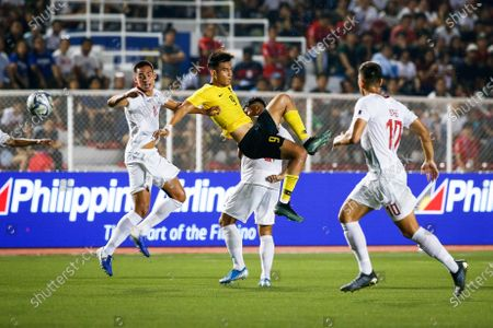 Muhammad Hadi Fayyadh Abdul Razak (C) of Malaysia in action against Filipino players Christian Rontini (L) and Justin Baas (R) during the SEA Games 2019 men's first round soccer match between the Philippines and Malaysia in Manila, Philippines, 29 November 2019.