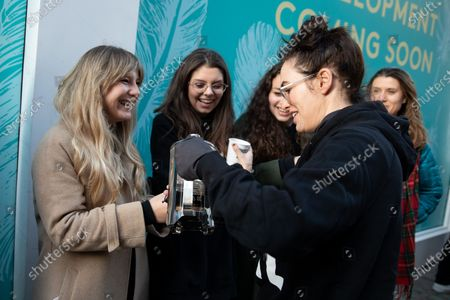Lena Headey pours hot drinks for people queuing at the official opening of the Choose Love store in Covent Garden