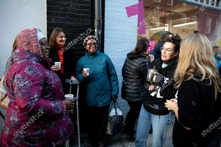 Stock Image of Lena Headey pours hot drinks for people queuing at the official opening of the Choose Love store in Covent Garden