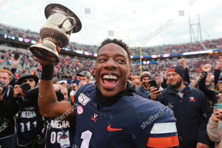 Virginia cornerback Nick Grant (1) holds the Commonwealth Cup as he and his team celebrate defeating Virginia Tech in Charlottesville, Va., . Virginia defeated Virginia Tech 39-30 for the first time in 15 years