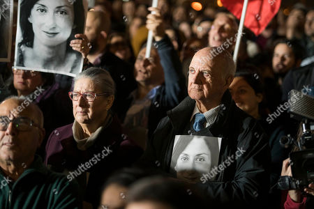 Rose and Michael Vella hold photos of their daughter, assassinated investigative journalist Daphne Caruana Galizia, as they partecipate in a demonstration in Valletta, Malta, Friday night, . The family of the journalist who was killed by a car bomb in Malta is urging Maltese Prime Minister Joseph Muscat to resign, after his former chief aide was released from jail in a probe aimed at finding the mastermind of the 2017 murder