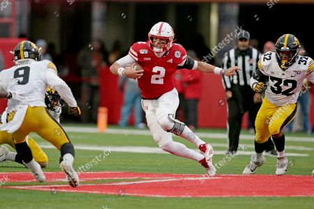 Nebraska quarterback Adrian Martinez (2) carries the ball between Iowa defensive back Geno Stone (9) and linebacker Djimon Colbert (32) during the first half of an NCAA college football game in Lincoln, Neb