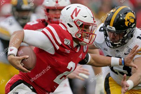 Joe Evans, Adrian Martinez. Nebraska quarterback Adrian Martinez (2) carries the ball against Iowa linebacker Joe Evans (13) during the first half of an NCAA college football game in Lincoln, Neb
