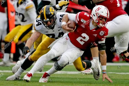 Kristian Welch, Adrian Martinez. Nebraska quarterback Adrian Martinez (2) breaks a tackle by Iowa linebacker Kristian Welch (34) during the first half of an NCAA college football game in Lincoln, Neb
