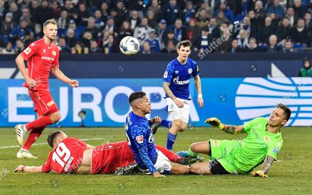 Union's Florian Hubner, Schalke's Amine Harit and Union's goalkeeper Rafal Gikiewicz, from left, challenge for the ball during the German Bundesliga soccer match between FC Schalke 04 and Union Berlin in Gelsenkirchen, Germany