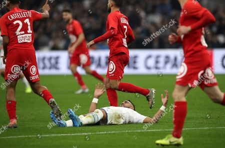 Marseille's Dimitri Payet lies on the pitch after falling during the French League One soccer match between Marseille and Brest at the Velodrome stadium in Marseille, southern France