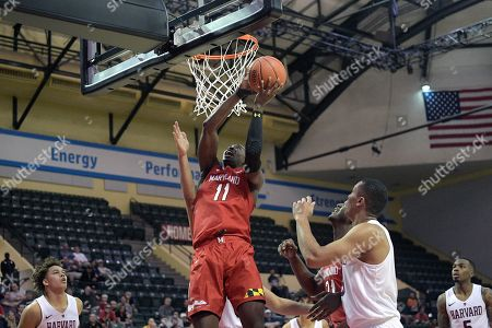Maryland guard Darryl Morsell (11) goes up for a shot between Harvard forward Chris Ledlum, left, and guard Justin Bassey during the second half of an NCAA college basketball game, in Lake Buena Vista, Fla