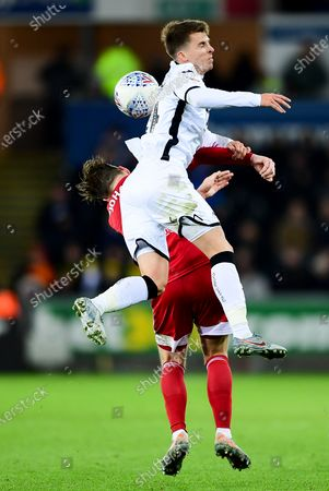 Tom Carroll of Swansea City contends for the aerial ball with Stefan Johansen of Fulham