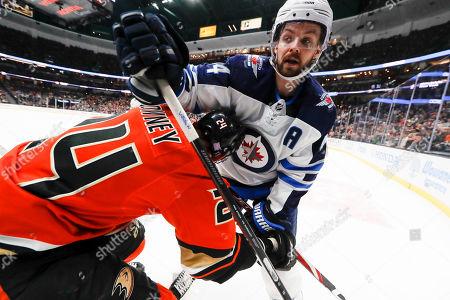 Winnipeg Jets defenseman Josh Morrissey, right, checks Anaheim Ducks right wing Carter Rowney during the second period of an NHL hockey game in Anaheim, Calif