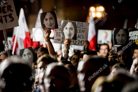 Protesters hold photos during a protest outside the office of the Prime Minster of Malta by civil groups Occupy Justice and Republica in Valletta, calling for the resignation of Malta Prime Minister Joseph Muscat after his chief of staff Keith Scembri was arrested and questioned regarding the murder of slain journalist Daphne Caruana Galizia. Muscat said Friday that police found no grounds to hold Keith Schembri, his former chief of staff in custody