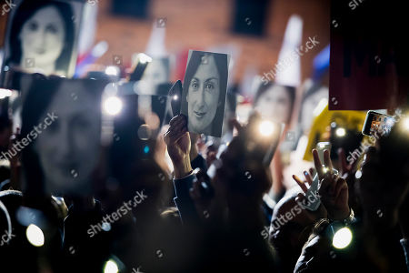 People hold pictures of slain journalist Daphne Caruana Galizia as they protest outside the office of the Maltese Prime Minister Joseph Muscat, calling for the resignation of Muscat, in Valletta, Malta., . The family of the journalist who was killed by a car bomb in Malta is urging Muscat to resign, after his former chief aide was released from jail in a probe aimed at finding the mastermind of the 2017 murder