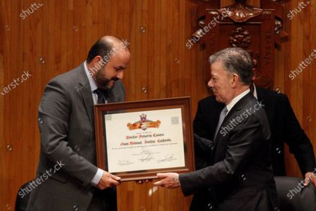 Former Colombian President Juan Manuel Santos (R) receives a honoris causa doctorate from the director of the Guadalajara University (UDG), in Guadalajara, Mexico, 29 November 2019. During the ceremony, Santos stated that the peace process between his government and the guerrilla of the Revolutionary Armed Forces of Colombia (FARC) was 'a process of empathy', that achieved reparations for the victims of the conflict.