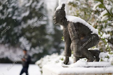 A sculpture titled 'New Starting point' by Chinese artist Liu Bolin is covered in snow in a park in Beijing, China, 30 November 2019. Beijing experienced its first snowfall for the winter on 29 November 2019.