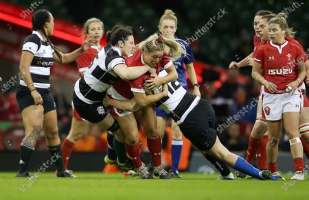 Kelsey Jones of Wales is tackled by Paula Fitzpatrick and Jenny Murphy of Barbarians.