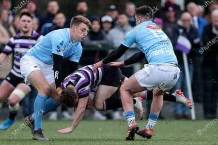Terenure College vs Garryowen. Terenure College's Stephen O'Neill is tackled by Liam Coombes and Jamie Heuston of Garryowen