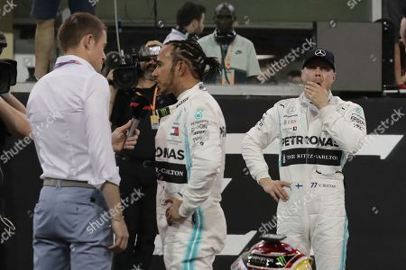 Mercedes driver Valtteri Bottas of Finland, right, reacts as Mercedes driver Lewis Hamilton of Britain speaks for television during the qualifying session at the Yas Marina racetrack in Abu Dhabi, United Arab Emirates, . The Emirates Formula One Grand Prix will take place on Sunday