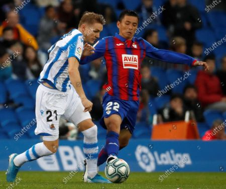 Real Sociedad's midfielder Martin Odegaard (L) duels for the ball with SD Eibar's Japanese Takashi Inui (R) during their Spanish LaLiga Primer Division soccer match played at Reale Arena stadium in San Sebastian, northern Spain, 30 November 2019.