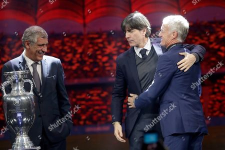 The coaches of Portugal Fernando Santos, Germany Joachim Loew and France Didier Deschamps, from left to right, who will play in group F, pose with the trophy after the draw for the UEFA Euro 2020 soccer tournament finals in Bucharest, Romania